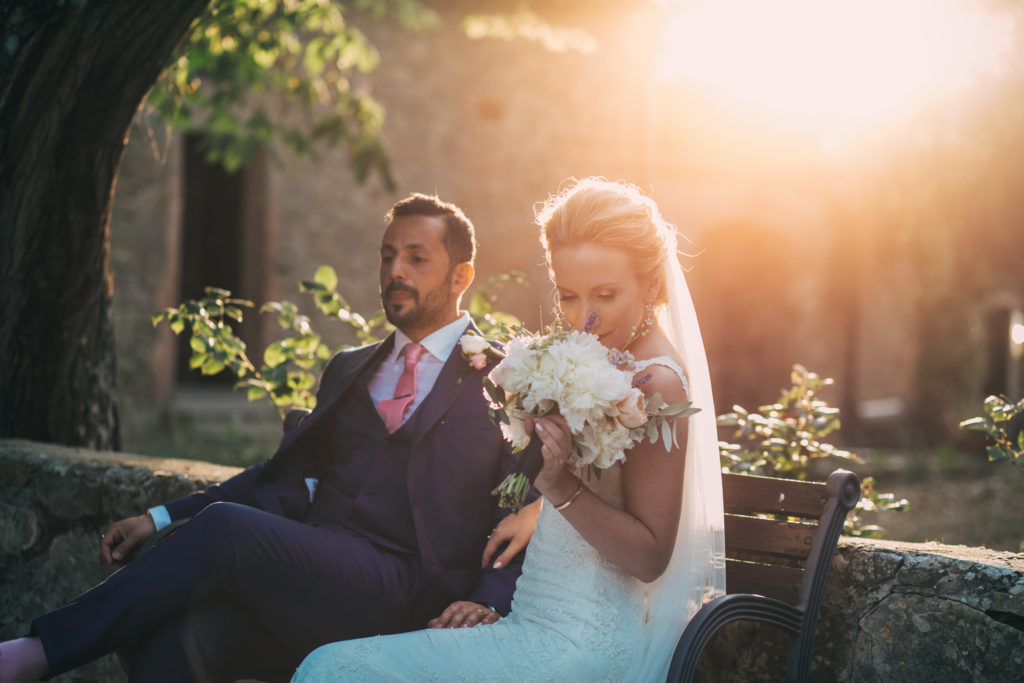 Beautiful bride with bouquet sitting on a bench at golden hour