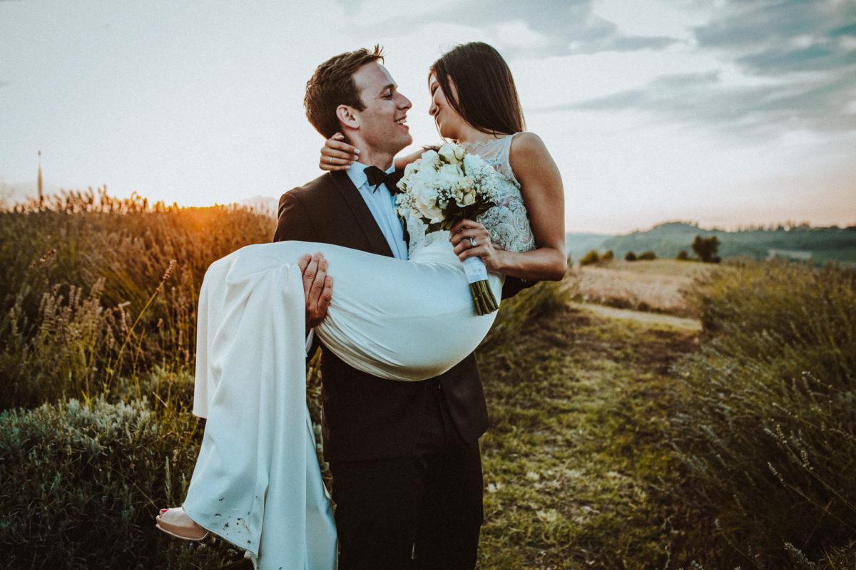 sposo prende in braccio sposa bellissima in un campo di lavanda
