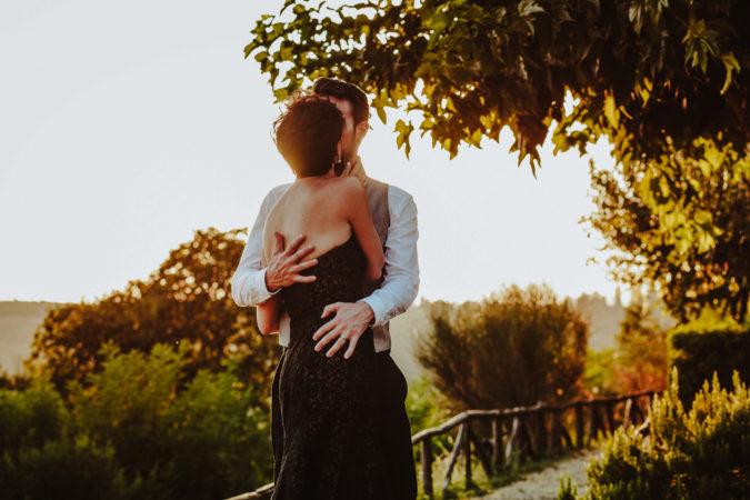 sposi che si abbracciano teneramente all'ombra di un grande albero