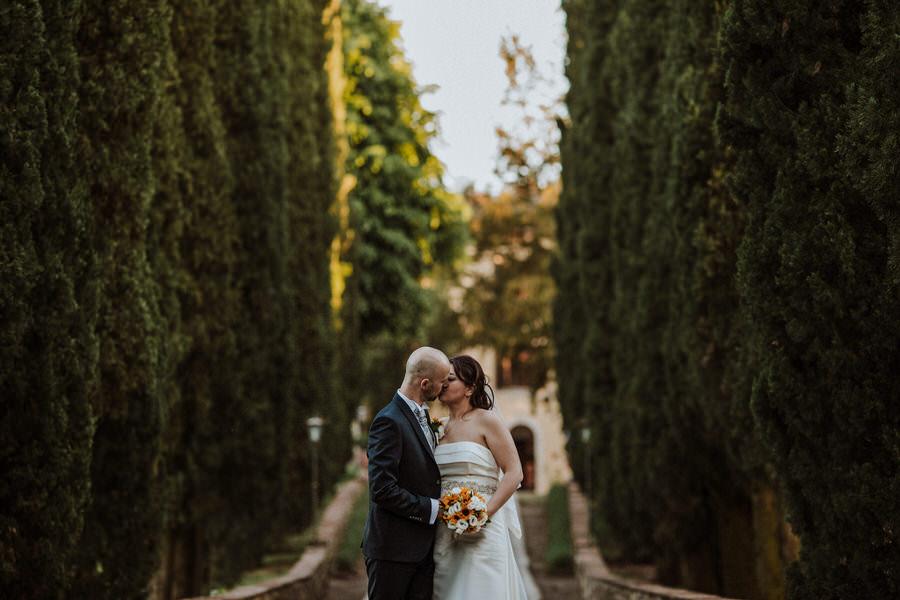 Sposi che si baciano lungo un viale di cipressi di una villa Toscana