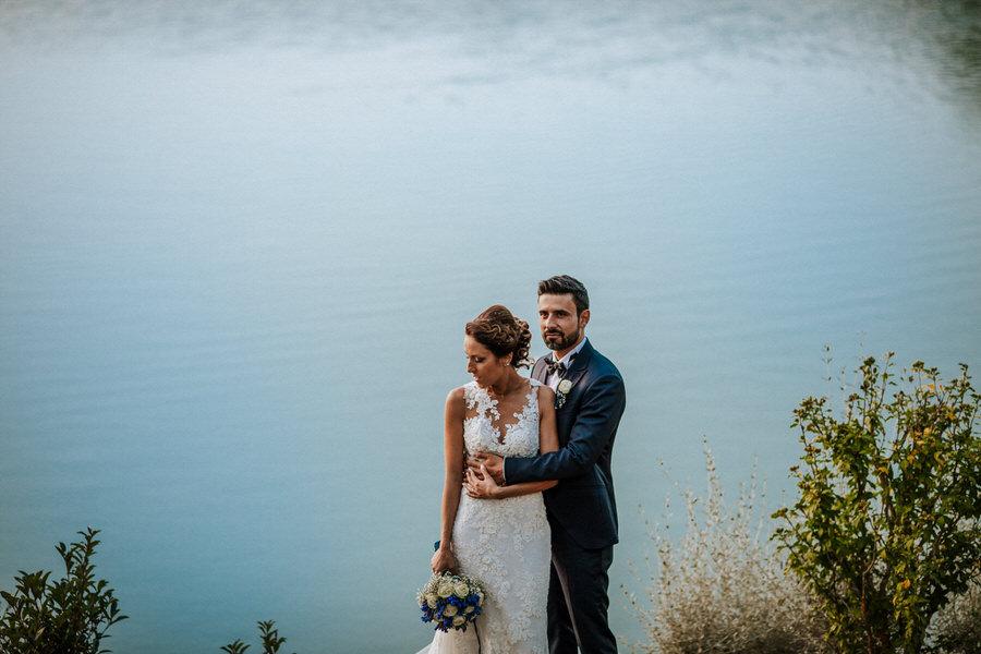 ritratto matrimoniale di coppia in riva al lago con acqua azzurra al crepuscolo