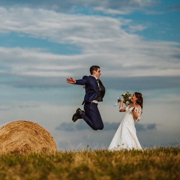 Sposo che salta in campo di grano vicino a rotoballe